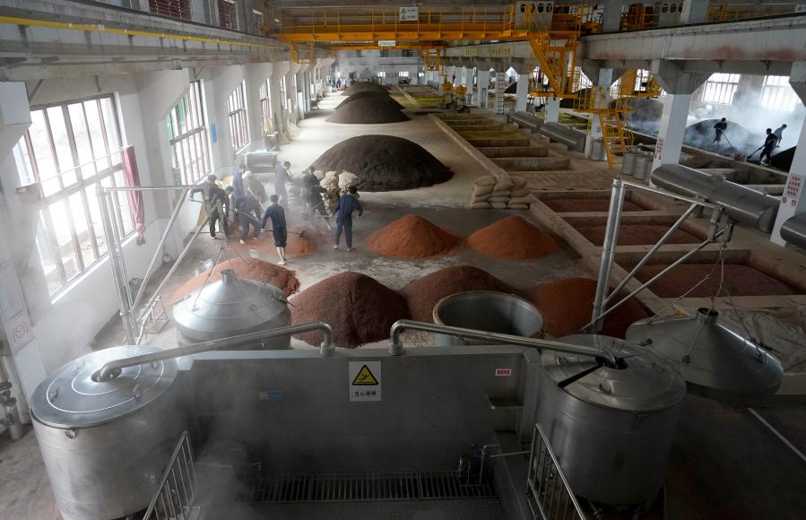 Workers mix grains with yeast at a distillery in Maotai town of Renhuai, southwest China's Guizhou Province, Nov. 28, 2020. Maotai is a small town in Renhuai City in mountainous Guizhou. What distinguishes it from other towns is that it produces a famous brand of Chinese liquor Moutai. The spirit, made from sorghum and wheat, takes up to one year for the whole production process, involving nine times of steaming, eight times of fermentation and seven times of distillation, before aged in clay pots. (Xinhua/Wang Yuguo)