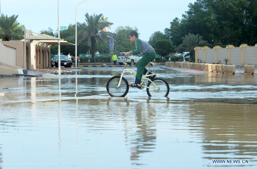 A boy rides a bicycle on a flooded street following heavy rains in Mubarak Al-Kabeer Governorate, Kuwait, on Nov. 29, 2020. Heavy rains hit Kuwait on Saturday evening and Sunday morning. (Photo by Asad/Xinhua)