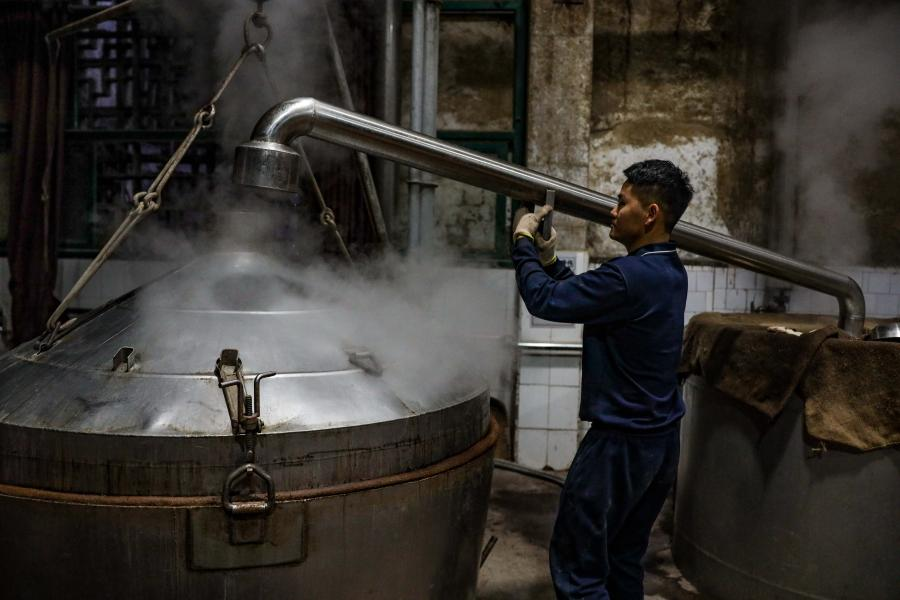 A man works at a distillery in Maotai town of Renhuai, southwest China's Guizhou Province, Nov. 28, 2020. Maotai is a small town in Renhuai City in mountainous Guizhou. What distinguishes it from other towns is that it produces a famous brand of Chinese liquor Moutai. The spirit, made from sorghum and wheat, takes up to one year for the whole production process, involving nine times of steaming, eight times of fermentation and seven times of distillation, before aged in clay pots. (Xinhua/Ou Dongqu)