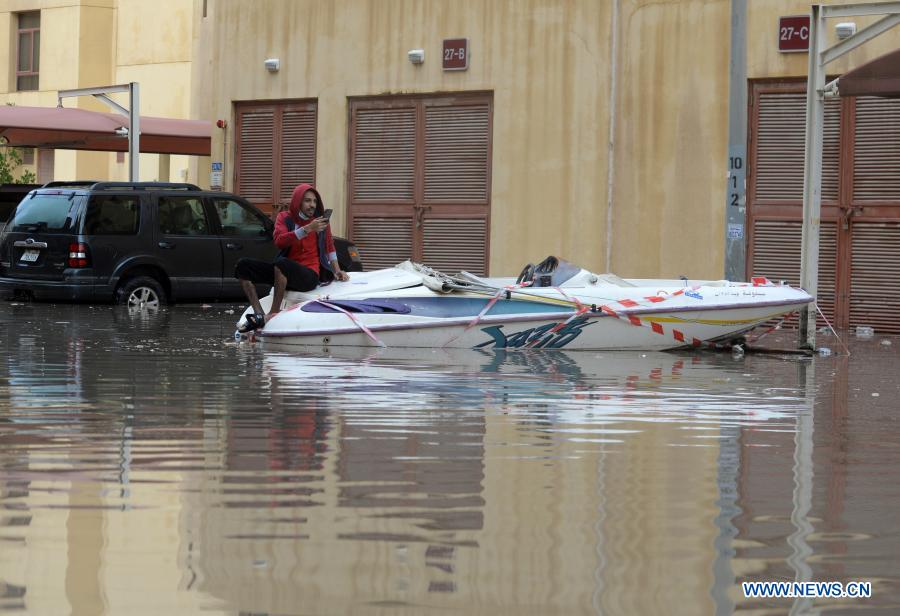 A man sits on a boat on a flooded street following heavy rains in Mubarak Al-Kabeer Governorate, Kuwait, on Nov. 29, 2020. Heavy rains hit Kuwait on Saturday evening and Sunday morning. (Photo by Asad/Xinhua)
