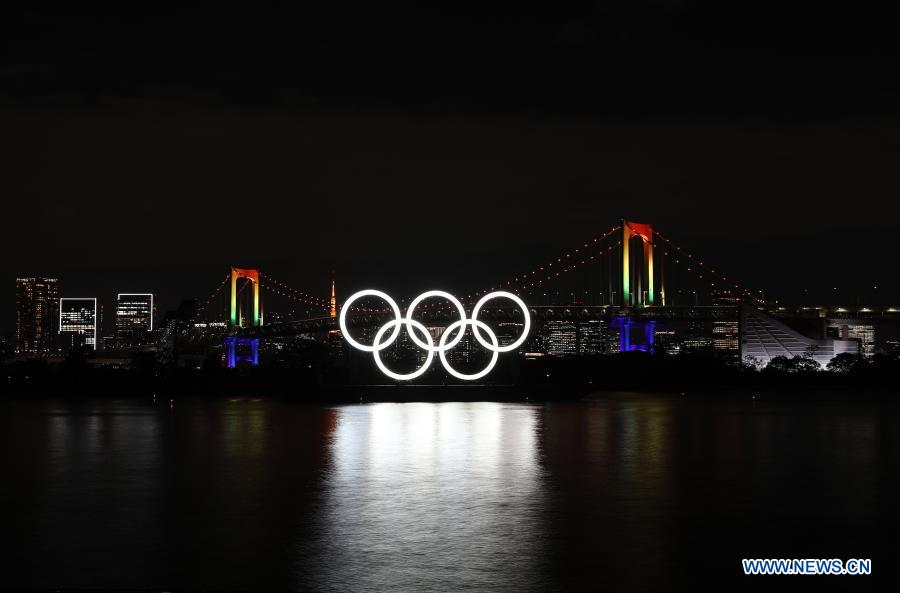 The illuminated Olympic rings, Rainbow Bridge and Tokyo Tower are seen at Tokyo Bay area, in Tokyo, Japan, Dec. 1, 2020. The giant Olympic rings returned to Tokyo Bay here on Tuesday about four months after being removed for safety and maintenance checks. The Rainbow Bridge is specially illuminated in rainbow colors. (Xinhua/Du Xiaoyi)