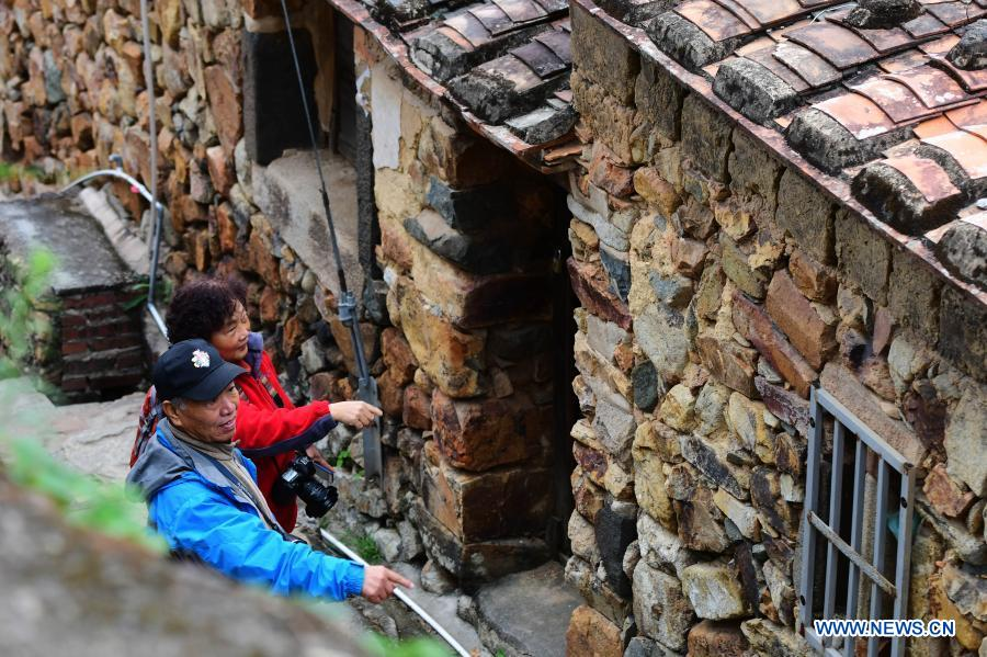 People visit the old buildings at Zhangjiao Village in Tuling Township of Quan'gang District, Quanzhou City, southeast China's Fujian Province, Dec. 1, 2020. Zhangjiao Village, located in the northwest mountainous area of Tuling Township, has a unique scenery with its stone houses stacked on top of each other. In recent years, Quan'gang District has made full use of the characteristic resources of Zhangjiao Village to develop ecological leisure tourism and promote the construction of beautiful countryside. (Xinhua/Wei Peiquan)