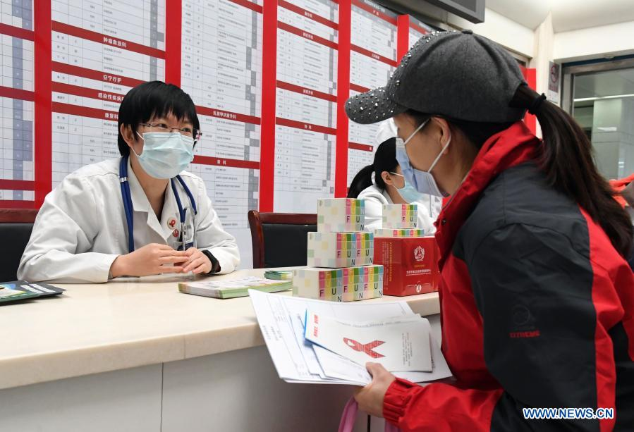 A visitor learns AIDS prevention know-hows during an AIDS awareness campaign held on the occasion of World AIDS Day at Haidian Hospital in Beijing, capital of China, Dec. 1, 2020. (Xinhua/Ren Chao)