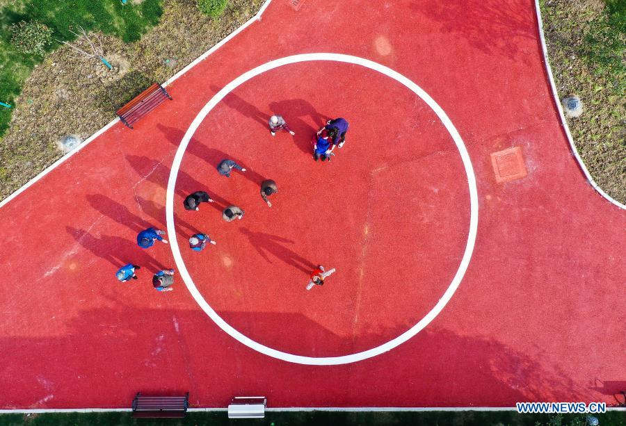 Aerial photo taken on Dec. 1, 2020 shows staff members organizing outdoor activities for seniors at a community elderly care center at the Suzhou Industrial Park in Suzhou, east China's Jiangsu Province. The elderly care center recently welcomed its clients back upon completion of a two-year renovation project that had fundamentally upgraded this facility from an ordinary nursing home. A professional management and operation team was also introduced to ensure quality services to the senior people living there. (Xinhua/Ji Chunpeng)