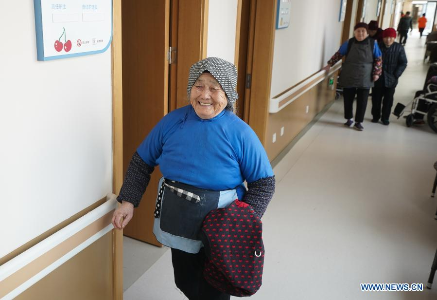 Senior people walk in the corridor of a community elderly care center at the Suzhou Industrial Park in Suzhou, east China's Jiangsu Province, Dec. 1, 2020. The elderly care center recently welcomed its clients back upon completion of a two-year renovation project that had fundamentally upgraded this facility from an ordinary nursing home. A professional management and operation team was also introduced to ensure quality services to the senior people living there. (Xinhua/Ji Chunpeng)
