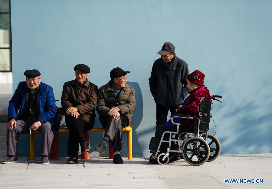 Senior people chat outside a community elderly care center at the Suzhou Industrial Park in Suzhou, east China's Jiangsu Province, Dec. 1, 2020. The elderly care center recently welcomed its clients back upon completion of a two-year renovation project that had fundamentally upgraded this facility from an ordinary nursing home. A professional management and operation team was also introduced to ensure quality services to the senior people living there. (Xinhua/Ji Chunpeng)