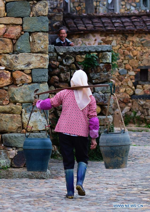 A villager walks past stone houses in Zhangjiao Village in Tuling Township of Quan'gang District, Quanzhou City, southeast China's Fujian Province, on Dec. 1, 2020. Zhangjiao Village, located in the northwest mountainous area of Tuling Township, has a unique scenery with its stone houses stacked on top of each other. In recent years, Quan'gang District has made full use of the characteristic resources of Zhangjiao Village to develop ecological leisure tourism and promote the construction of beautiful countryside. (Xinhua/Wei Peiquan)