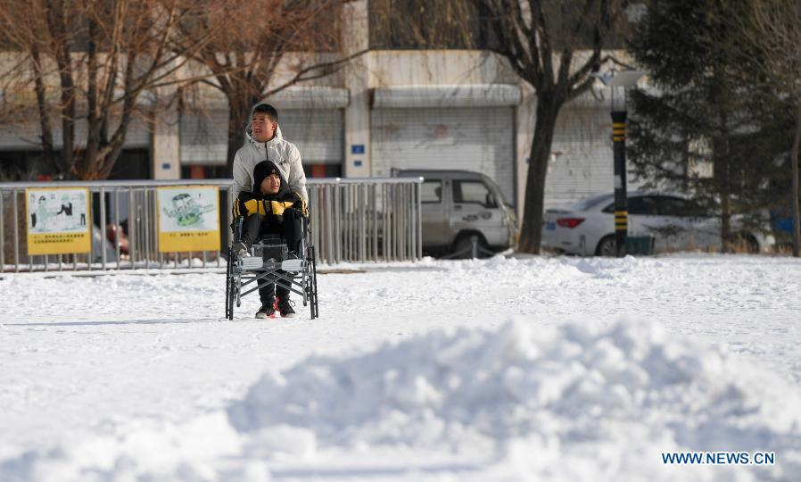 Sun Simiao and Wang Aoran take a walk at a square in Chifeng City, north China's Inner Mongolia Autonomous Region, Nov. 26, 2020. Wang Aoran, 15, has been disabled in action by creatine kinase abnormality since he was a child. When in the second grade of primary school, he received help from schoolmate Sun Simiao, who voluntarily began to carry him from the school gate to his classroom. He has been helping him ever since. The two became inseparable best friends. They went to the same middle school, both in the same class, and they even became deskmates. Now Wang is also helped by other classmates and the teachers.