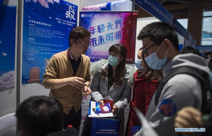 Job seekers communicate with a staff member from an enterprise at a job fair in the Hongshan Gymnasium in Wuhan, central China's Hubei Province, Dec. 2, 2020. A national colleage graduates employment and entrepreneurship promotion fair kicked off here on Wednesday. Over 500,000 jobs vacancies were offered to applicants. (Xinhua/Xiao Yijiu)