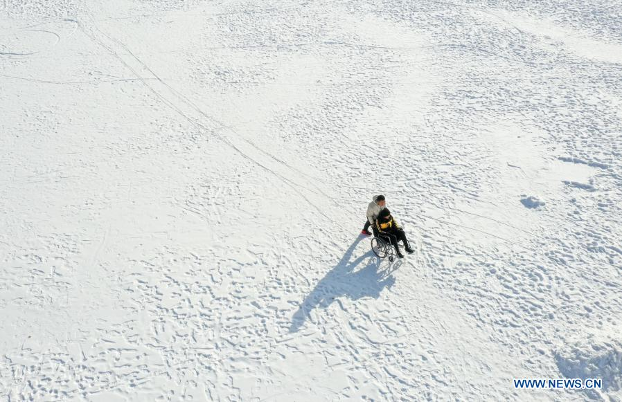 In this aerial photo, Sun Simiao pushes Wang Aoran in a wheelchair at a square in Chifeng City, north China's Inner Mongolia Autonomous Region, Nov. 26, 2020. Wang Aoran, 15, has been disabled in action by creatine kinase abnormality since he was a child. When in the second grade of primary school, he received help from schoolmate Sun Simiao, who voluntarily began to carry him from the school gate to his classroom. He has been helping him ever since. The two became inseparable best friends. They went to the same middle school, both in the same class, and they even became deskmates. Now Wang is also helped by other classmates and the teachers.