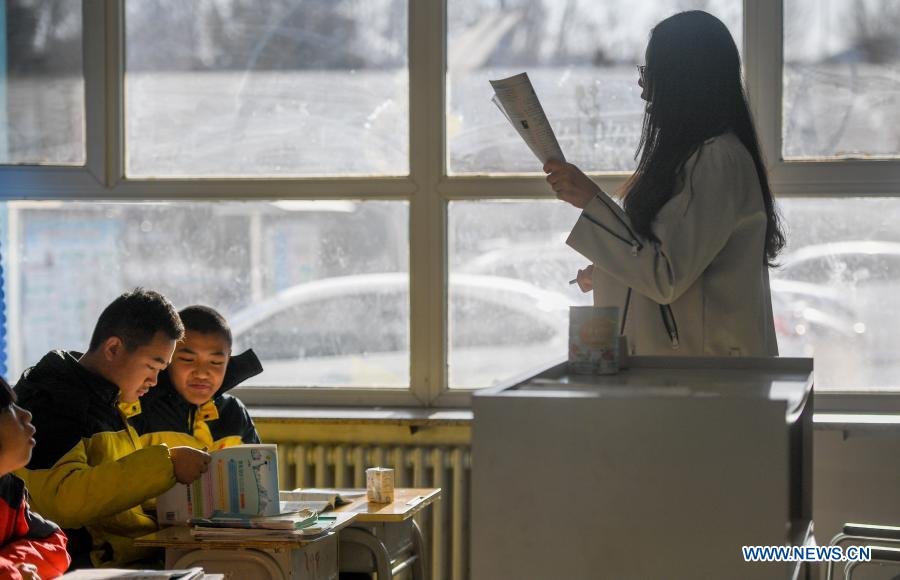 Sun Simiao (1st, L) and Wang Aoran (2nd, L) are at class in the school in Chifeng City, north China's Inner Mongolia Autonomous Region, Nov. 25, 2020. Wang Aoran, 15, has been disabled in action by creatine kinase abnormality since he was a child. When in the second grade of primary school, he received help from schoolmate Sun Simiao, who voluntarily began to carry him from the school gate to his classroom. He has been helping him ever since. The two became inseparable best friends. They went to the same middle school, both in the same class, and they even became deskmates. Now Wang is also helped by other classmates and the teachers.