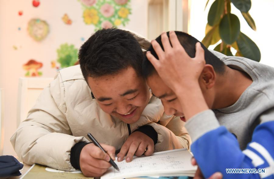 Sun Simiao (L) reads with Wang Aoran at Wang's home in Chifeng City, north China's Inner Mongolia Autonomous Region, Nov. 25, 2020. Wang Aoran, 15, has been disabled in action by creatine kinase abnormality since he was a child. When in the second grade of primary school, he received help from schoolmate Sun Simiao, who voluntarily began to carry him from the school gate to his classroom. He has been helping him ever since. The two became inseparable best friends. They went to the same middle school, both in the same class, and they even became deskmates. Now Wang is also helped by other classmates and the teachers.