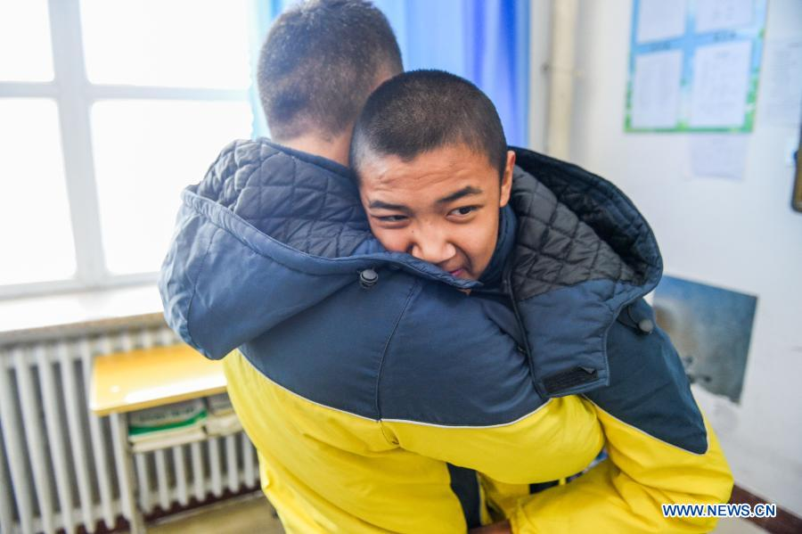Sun Simiao holds Wang Aoran and prepares to help him leave school in Chifeng City, north China's Inner Mongolia Autonomous Region, Nov. 25, 2020. Wang Aoran, 15, has been disabled in action by creatine kinase abnormality since he was a child. When in the second grade of primary school, he received help from schoolmate Sun Simiao, who voluntarily began to carry him from the school gate to his classroom. He has been helping him ever since. The two became inseparable best friends. They went to the same middle school, both in the same class, and they even became deskmates. Now Wang is also helped by other classmates and the teachers.