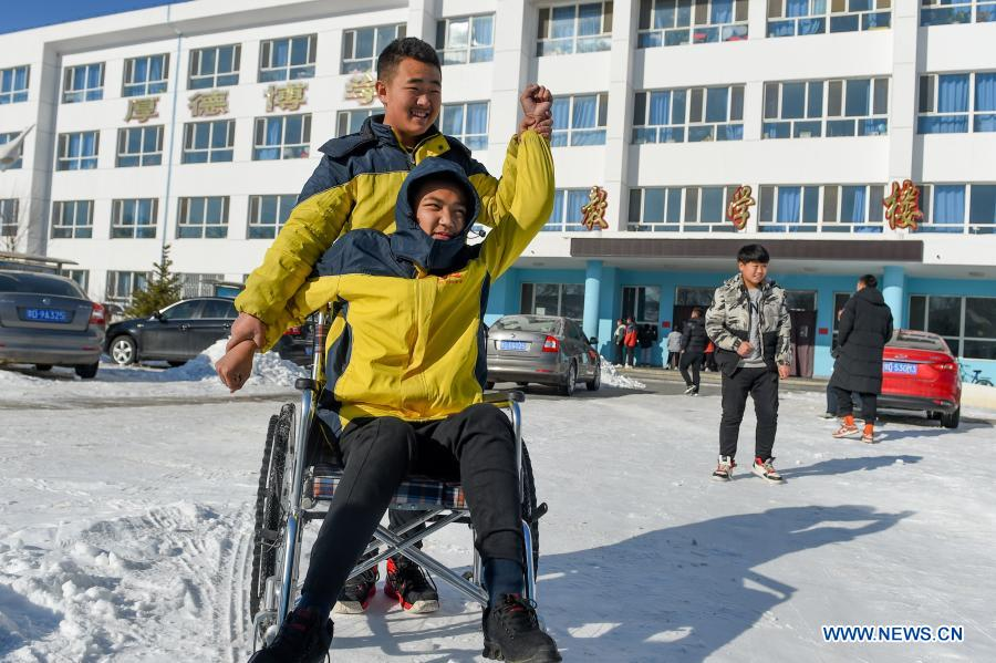 Sun Simiao helps Wang Aoran do exercise in the school in Chifeng City, north China's Inner Mongolia Autonomous Region, Nov. 25, 2020. Wang Aoran, 15, has been disabled in action by creatine kinase abnormality since he was a child. When in the second grade of primary school, he received help from schoolmate Sun Simiao, who voluntarily began to carry him from the school gate to his classroom. He has been helping him ever since. The two became inseparable best friends. They went to the same middle school, both in the same class, and they even became deskmates. Now Wang is also helped by other classmates and the teachers.