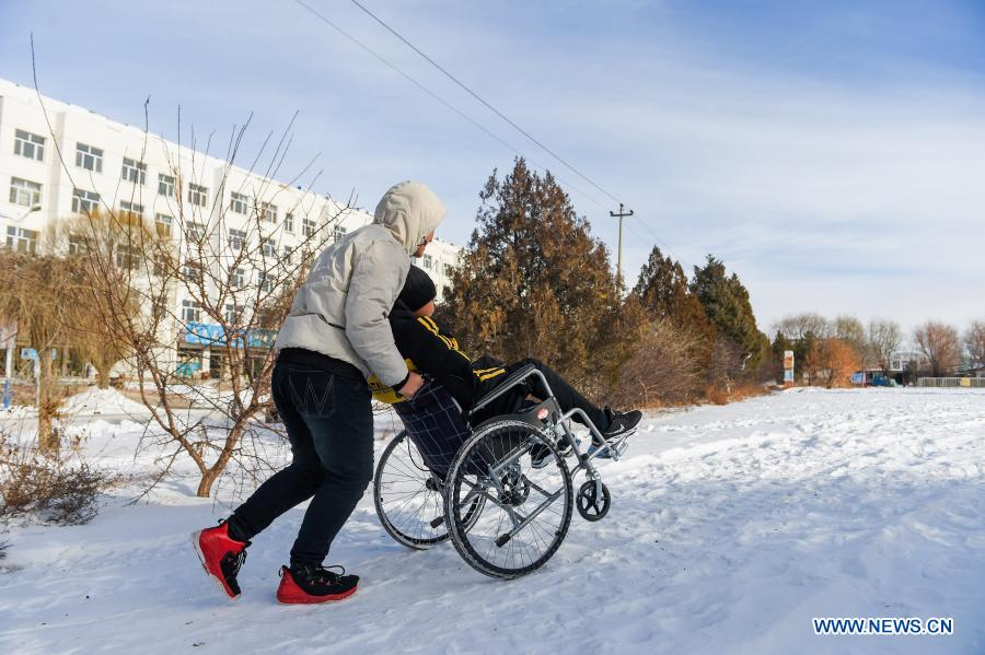 Sun Simiao pushes Wang Aoran in a wheelchair to play at a square in Chifeng City, north China's Inner Mongolia Autonomous Region, Nov. 26, 2020. Wang Aoran, 15, has been disabled in action by creatine kinase abnormality since he was a child. When in the second grade of primary school, he received help from schoolmate Sun Simiao, who voluntarily began to carry him from the school gate to his classroom. He has been helping him ever since. The two became inseparable best friends. They went to the same middle school, both in the same class, and they even became deskmates. Now Wang is also helped by other classmates and the teachers.