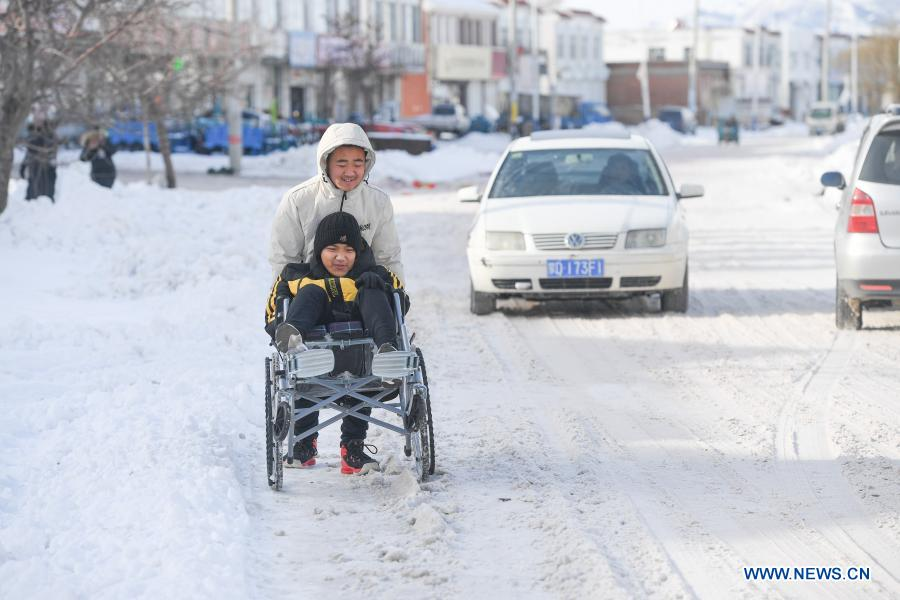 Sun Simiao pushes Wang Aoran in a wheelchiar on a street in Chifeng City, north China's Inner Mongolia Autonomous Region, Nov. 26, 2020. Wang Aoran, 15, has been disabled in action by creatine kinase abnormality since he was a child. When in the second grade of primary school, he received help from schoolmate Sun Simiao, who voluntarily began to carry him from the school gate to his classroom. He has been helping him ever since. The two became inseparable best friends. They went to the same middle school, both in the same class, and they even became deskmates. Now Wang is also helped by other classmates and the teachers.