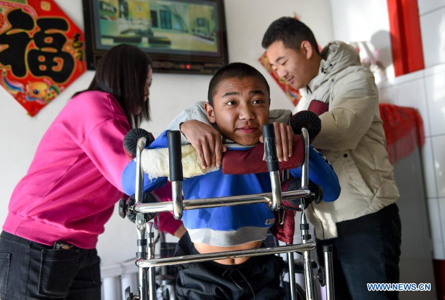 Sun Simiao (R) and Wang Aoran's mother help Wang in recovery training in Chifeng City, north China's Inner Mongolia Autonomous Region, Nov. 26, 2020. Wang Aoran, 15, has been disabled in action by creatine kinase abnormality since he was a child. When in the second grade of primary school, he received help from schoolmate Sun Simiao, who voluntarily began to carry him from the school gate to his classroom. He has been helping him ever since. The two became inseparable best friends. They went to the same middle school, both in the same class, and they even became deskmates. Now Wang is also helped by other classmates and the teachers.