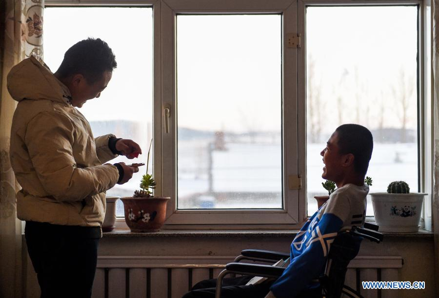 Sun Simiao (L) plays with Wang Aoran at Wang's home in Chifeng City, north China's Inner Mongolia Autonomous Region, Nov. 25, 2020. Wang Aoran, 15, has been disabled in action by creatine kinase abnormality since he was a child. When in the second grade of primary school, he received help from schoolmate Sun Simiao, who voluntarily began to carry him from the school gate to his classroom. He has been helping him ever since. The two became inseparable best friends. They went to the same middle school, both in the same class, and they even became deskmates. Now Wang is also helped by other classmates and the teachers.