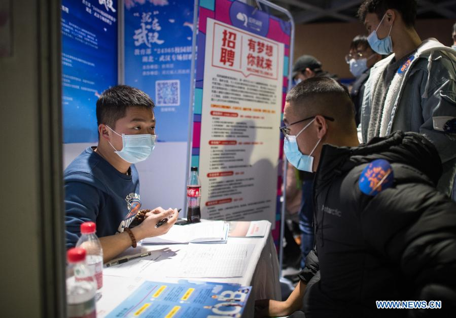 A job seeker communicates with a staff member from an enterprise at a job fair in the Hongshan Gymnasium in Wuhan, central China's Hubei Province, Dec. 2, 2020. A national colleage graduates employment and entrepreneurship promotion fair kicked off here on Wednesday. Over 500,000 jobs vacancies were offered to applicants. (Xinhua/Xiao Yijiu)