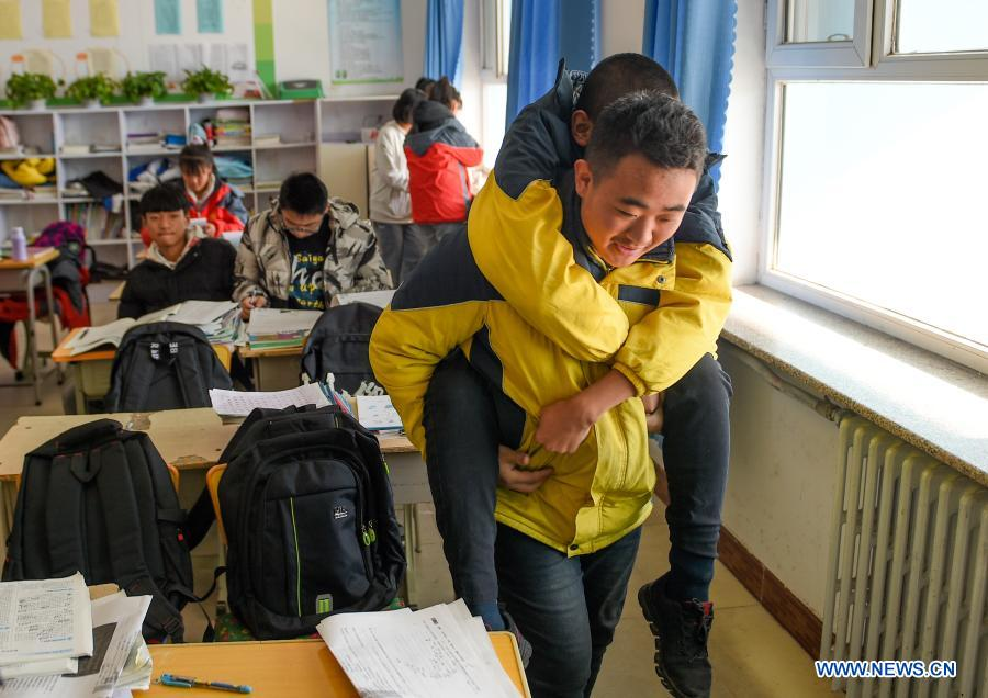 Sun Simiao carries Wang Aoran for outdoor activities in the school at Chifeng City, north China's Inner Mongolia Autonomous Region, Nov. 25, 2020. Wang Aoran, 15, has been disabled in action by creatine kinase abnormality since he was a child. When in the second grade of primary school, he received help from schoolmate Sun Simiao, who voluntarily began to carry him from the school gate to his classroom. He has been helping him ever since. The two became inseparable best friends. They went to the same middle school, both in the same class, and they even became deskmates. Now Wang is also helped by other classmates and the teachers.