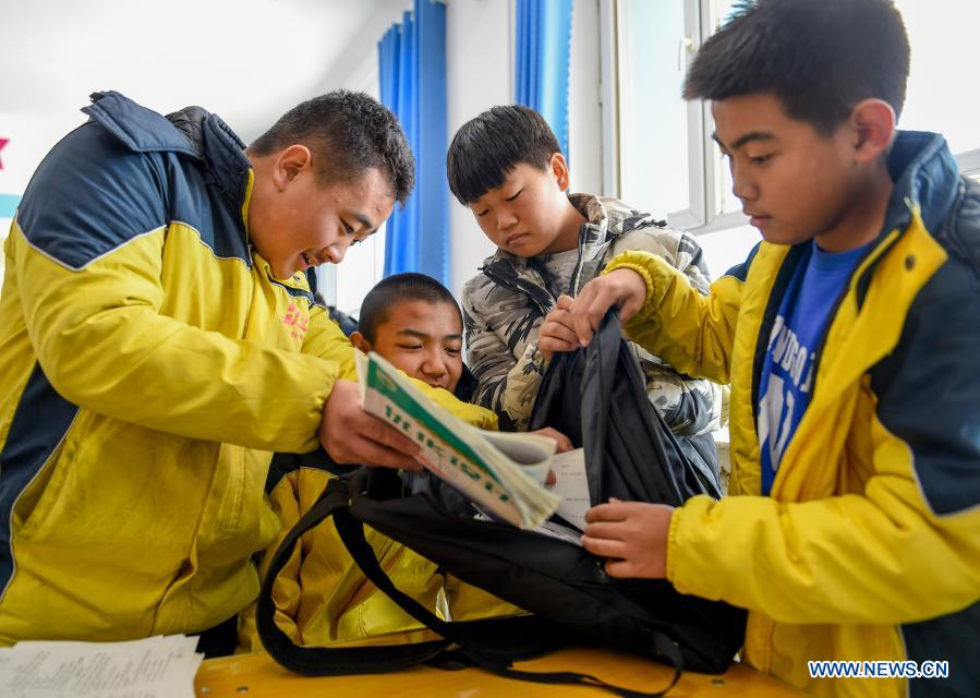 Sun Simiao (1st, L) and his classmates help Wang Aoran pack his schoolbag in the school at Chifeng City, north China's Inner Mongolia Autonomous Region, Nov. 25, 2020. Wang Aoran, 15, has been disabled in action by creatine kinase abnormality since he was a child. When in the second grade of primary school, he received help from schoolmate Sun Simiao, who voluntarily began to carry him from the school gate to his classroom. He has been helping him ever since. The two became inseparable best friends. They went to the same middle school, both in the same class, and they even became deskmates. Now Wang is also helped by other classmates and the teachers.