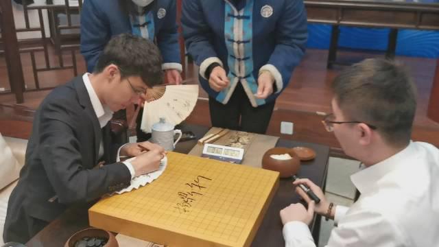 杨鼎新连笑为比赛棋盘签字
