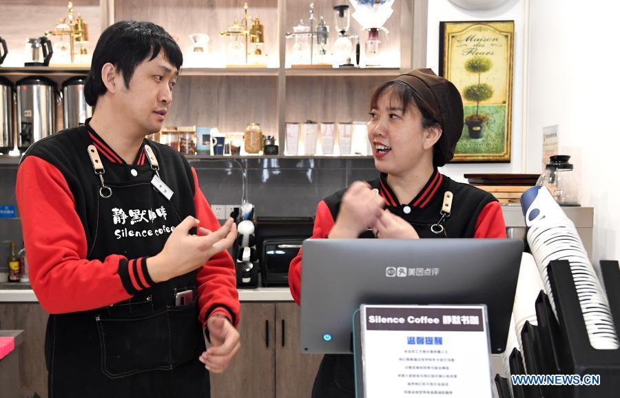 Staff members Li Tao (L) and Cao Ruihua communicate with sign language in Silence Coffee in Xincheng District of Xi'an, northwest China's Shaanxi Province, Dec. 1, 2020. Silence Coffee, a coffee shop opened in Xi'an more than two months ago, is also a business incubator established for disabled people. Three of the four staff members in Silence Coffee are hearing-impaired baristas. They communicate with customers with sign language or typing on cellphone. Working on two shifts, all four members carried out routine work in the coffee shop including coffee making, baking, guest receiving and cleaning. Wang Lichao, manager of Silence Coffee, has learned sign language so as to better guide and