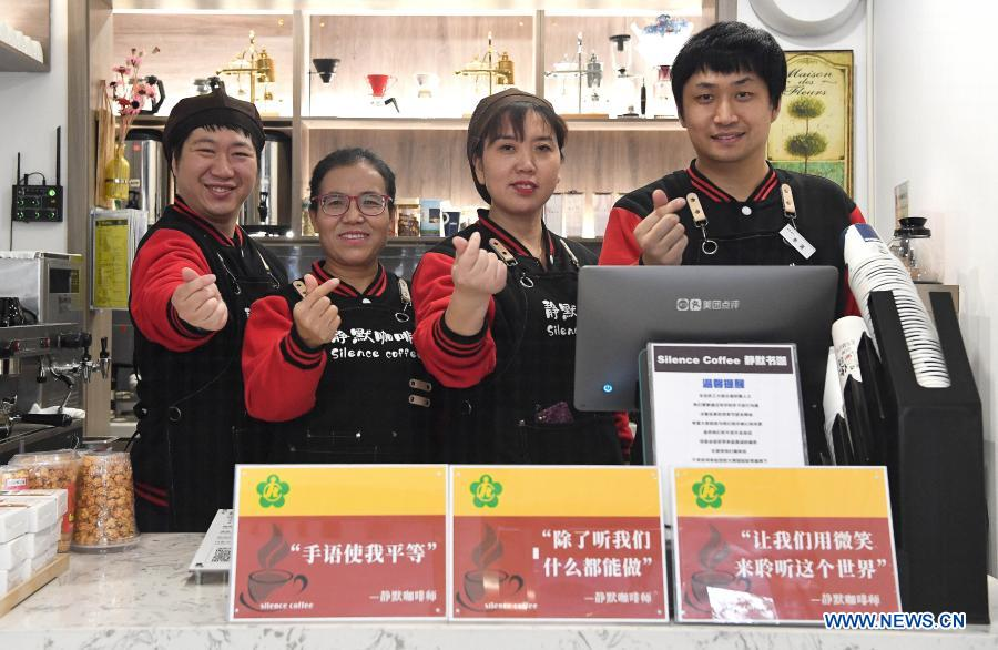Staff members Yao Yixuan, Wang Lichao, Cao Ruihua and Li Tao (from L to R) pose for a photo in Silence Coffee in Xincheng District of Xi'an, northwest China's Shaanxi Province, Dec. 1, 2020. Silence Coffee, a coffee shop opened in Xi'an more than two months ago, is also a business incubator established for disabled people. Three of the four staff members in Silence Coffee are hearing-impaired baristas. They communicate with customers with sign language or typing on cellphone. Working on two shifts, all four members carried out routine work in the coffee shop including coffee making, baking, guest receiving and cleaning. Wang Lichao, manager of Silence Coffee, has learned sign language so as to better guide and