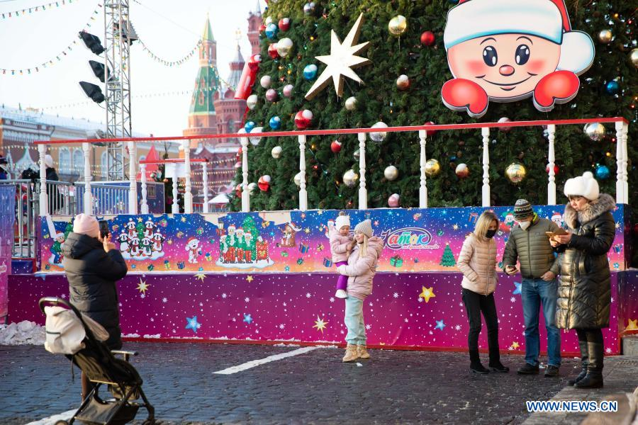 People take photos by a Christmas tree with New Year decorations in Moscow, Russia, on Dec. 2, 2020. (Xinhua/Bai Xueqi)