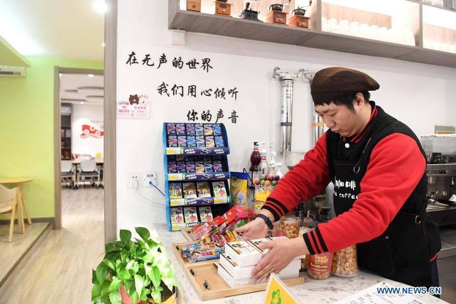 Staff member Yao Yixuan arranges the counter in Silence Coffee in Xincheng District of Xi'an, northwest China's Shaanxi Province, Dec. 1, 2020. Silence Coffee, a coffee shop opened in Xi'an more than two months ago, is also a business incubator established for disabled people. Three of the four staff members in Silence Coffee are hearing-impaired baristas. They communicate with customers with sign language or typing on cellphone. Working on two shifts, all four members carried out routine work in the coffee shop including coffee making, baking, guest receiving and cleaning. Wang Lichao, manager of Silence Coffee, has learned sign language so as to better guide and