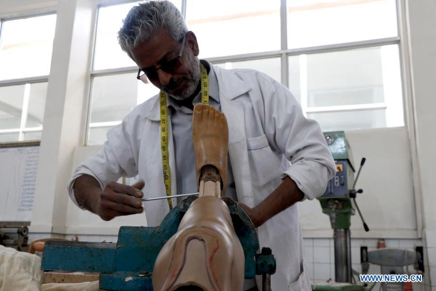 A technician prepares a prosthetic limb for a disabled man at the rehabilitation center in Sanaa, Yemen, on Dec. 2, 2020. The world observes the International Day of Persons with Disabilities on Dec. 3. (Photo by Mohammed Mohammed/Xinhua)