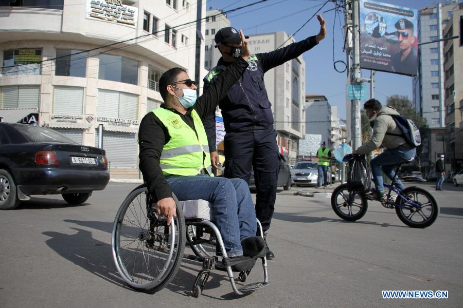A man with disability directs traffic with the guidance of a traffic policeman, in Gaza City, Dec. 2, 2020. The world observes the International Day of Persons with Disabilities on Dec. 3. (Photo by Rizek Abdeljawad/Xinhua)