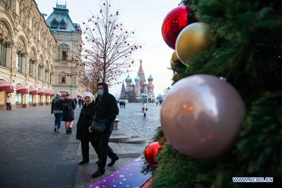 People walk by a Christmas tree with New Year decorations in Moscow, Russia, on Dec. 2, 2020. (Xinhua/Bai Xueqi)