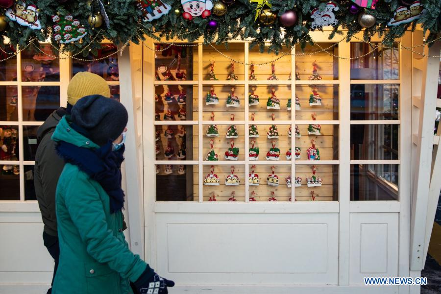 People walk by a store which sells New Year decorations in Moscow, Russia, on Dec. 2, 2020. (Xinhua/Bai Xueqi)
