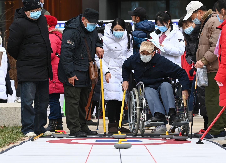 12月2日,来自北京市基层社区的残疾人及亲属,与冬残奥会冠军、北京冬奥组委青年团员一起开展了旱地冰球、桌上冰壶、陆上冰壶、冰蹴球和雪上项目VR体验等趣味冰雪活动。新京报记者 陶冉 摄