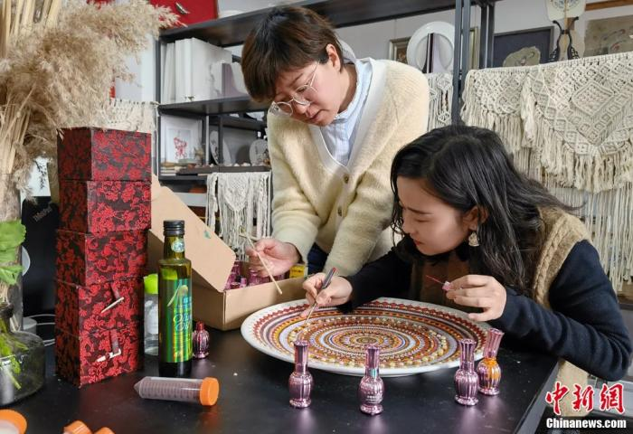 圖為蘭州交通大學藝術設計學院副教授梁艷指導學生制作敦煌彩繪工藝盤。
