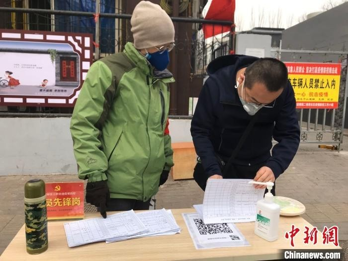 """杨代华被安排值守小区,检查出入人员的""""出入证""""。 李怡 摄"""