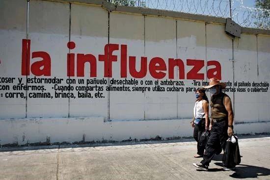 2009年,墨西哥城,戴着防护性外科口罩的民众走过甲型H1N1流感警告标志。