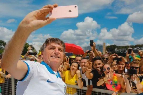 ▲博索纳罗15日在巴西利亚的游行中与支持者自拍合影。(法新社)