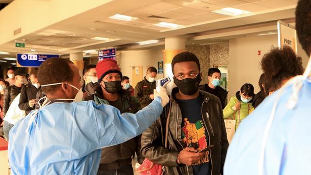 肯尼亚医护人员在内罗毕肯雅塔国际机场对旅客进行测温。