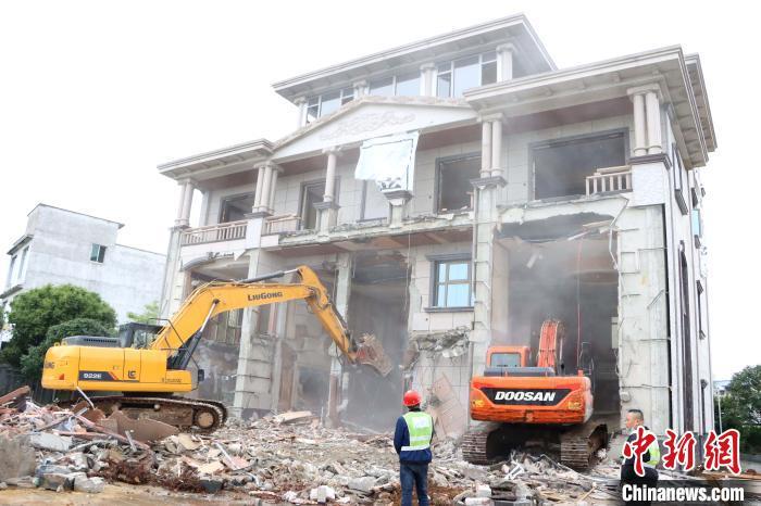 图为挖掘机在拆除大毒枭张加爱涉毒涉黑违法建筑。 徐肖玲 摄
