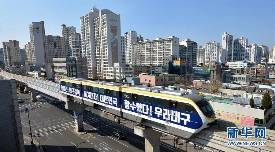 ▲3月23日,在韩国大邱,一辆车身印有加油字样的地铁三号线列车从市区驶过。新华社/纽西斯通讯社