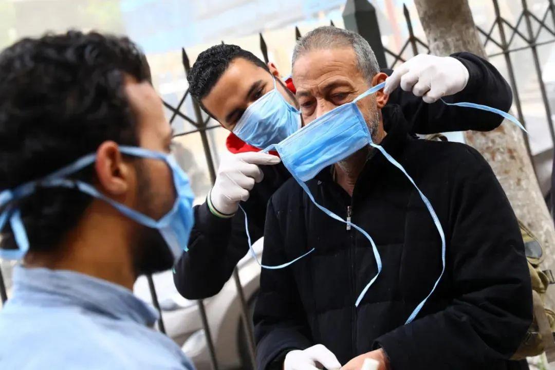 ▲3月20日,在埃及开罗,志愿者帮助市民佩戴口罩。新华社发(艾哈迈德·戈马摄)