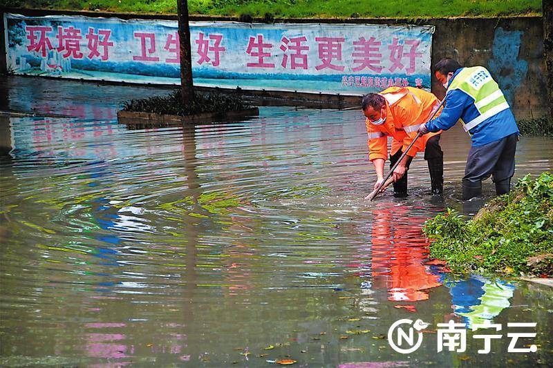 市政工作人员在积水中打开井盖排水。记者 宋延康 摄
