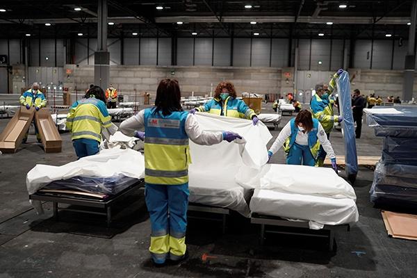 3月22日,在西班牙马德里,医务人员在马德里会展中心改造成的野战医院中准备病床。新华社 图