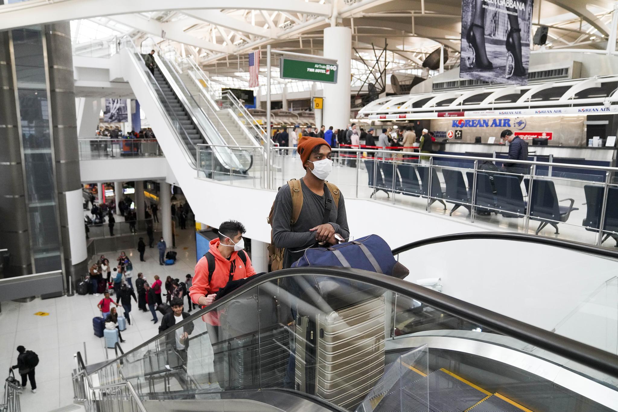 3月13日,在美国纽约肯尼迪国际机场,乘客坐电梯上楼。