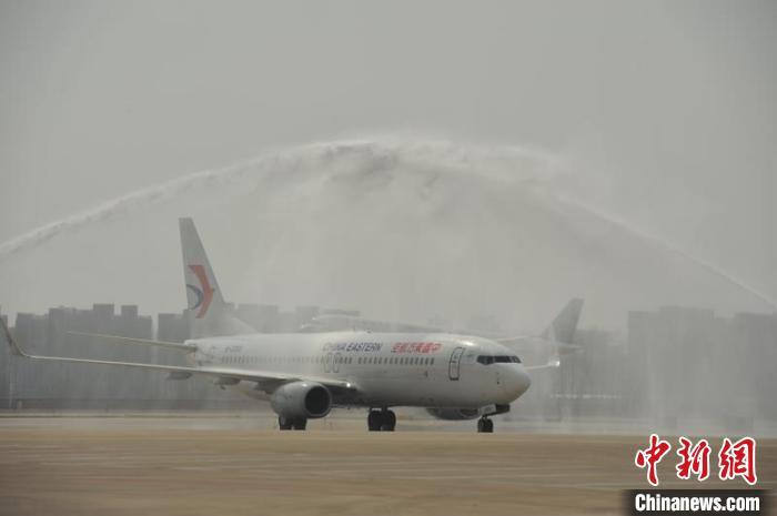 """机场的""""过水门""""仪式为他们接风洗尘。 胡静 摄"""