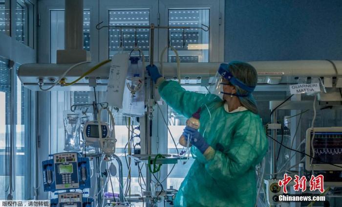 资料图:当地时间3月23日,意大利米兰东南部的克雷莫纳医院重症监护室,医护人员正在为感染新冠状肺炎的重症患者治疗。