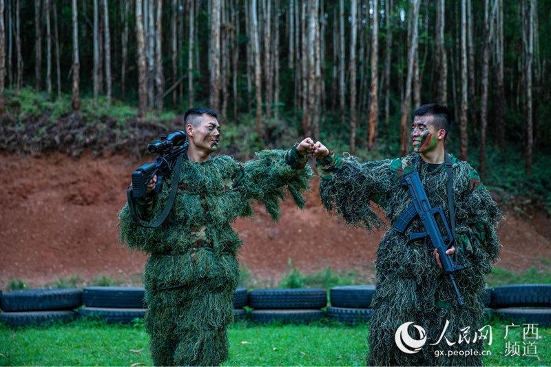图为完成潜伏狙击任务后的乐聚(左)和许海鹏(右)击拳互勉。余海洋摄