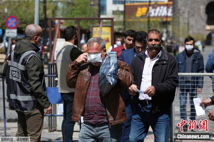 当地时间4月9日,在土耳其迪亚巴克尔,人们从市政工作人员那里获得免费口罩。